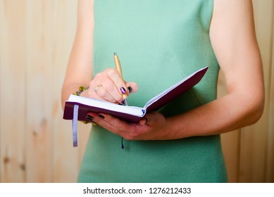 Woman writes in a notebook her observations on work, thoughts and ideas for improving business strategies.