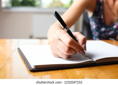 Woman writes in notebook at table. Concept writer.