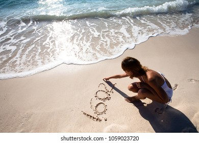 woman writes numbers on the beach