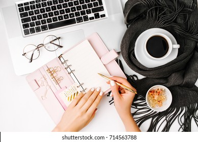 Woman writes in the planner. Workspace with laptop,  coffee cup wrapped in scarf, golden clips, glasses. Stylish office desk. Autumn or Winter concept.  Flat lay, top view