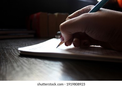 Woman writing in the book with a pencil