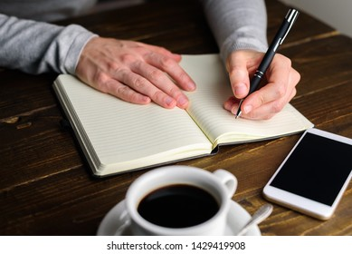Woman writing by left hand in notebook. Left hander day concept. Working place of lefty