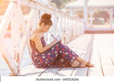Mulher escrevendo por caneta no bloco de notas no verão ensolarado