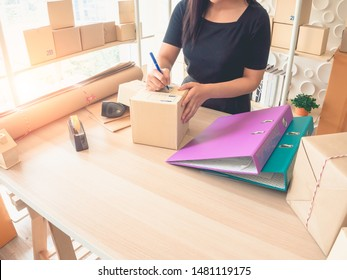 A woman is writing customer address on the box to send goods to her customer