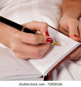 woman writing a diary while lying on the bed