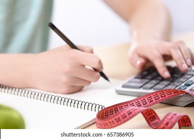 Woman writing a diet plan and calculating calories