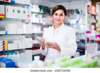 Woman is writing down assortment of drugs in pharmacy.