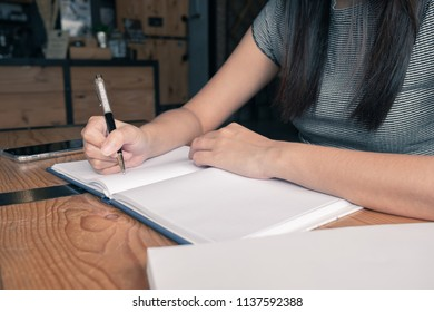 Woman writing down her idea on notebook in coffee shop