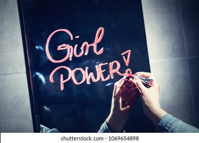 "Woman writing ""girl power"" on a mirror with red lipstick. Woman empowerment. Feminism."