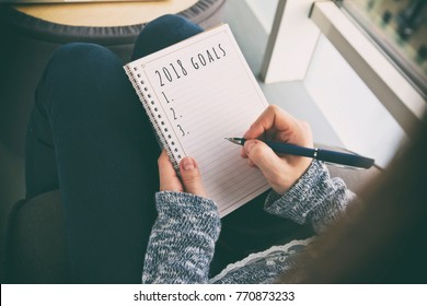 The woman is writing goals for 2018 year