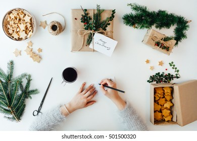 Woman writing Greeting Card for Christmas presents
