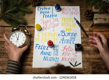 Woman writing happy new year in many different languages calligraphy