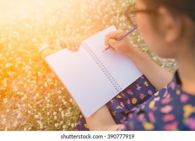 woman writing in her diary on the meadow with white flowers