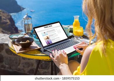 Woman writing her travel blog on laptop