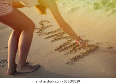 Woman writing inscriptions on beach sand - Summer vibes are coming