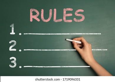 Woman writing list of rules on chalkboard, closeup