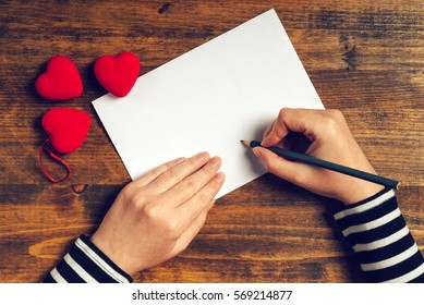 Woman writing love letter or romantic poem for Valentines day, top view of female hands