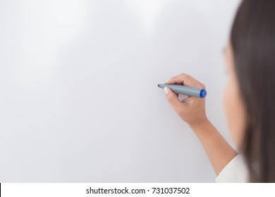 woman writing with a marker on a board