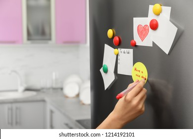 Woman writing message on note stuck to refrigerator door at home, closeup