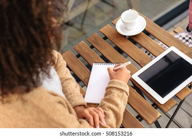 woman writing in the notepad while sitting at the table indoors