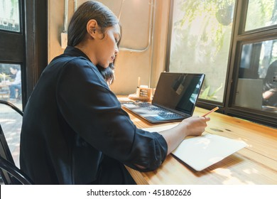 woman writing notes in her diary. Businesswoman sitting at her desk and taking notes.