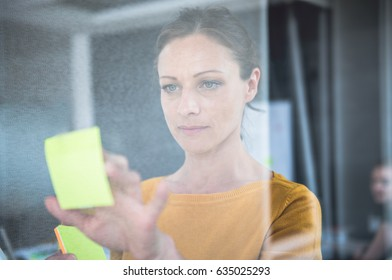 Woman writing notes on the glass board at the office