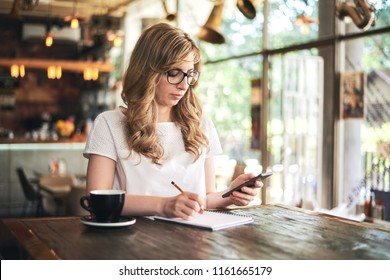 Woman writing on a notebook while holding her mobile phone