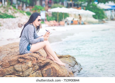 Woman writing on notepad with a pen at the beach.She sits at the rocks and wears sunglasses.