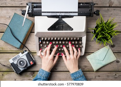 Woman writing on an old typewriter