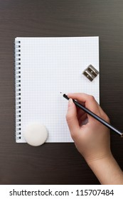 woman writing with pencil on notebook in the office