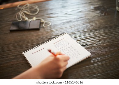 """Woman writing phrase """"Help me"""" on notebook in cafe"""