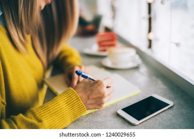 Woman writing pondering on creating publication writing in notepad. Young woman enjoying freelance work in cafe interior making notes of ideas in notepad. Toned image. Selective focus.