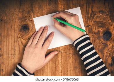 Woman writing sender address on mailing envelope, female hands from above on office desk sending letter, top view, retro toned.
