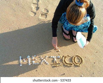 Woman writing with shells on beach