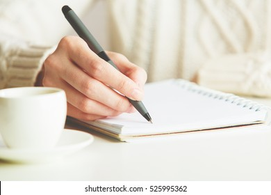 Woman writing in spiral notepad placed on bright desktop with coffee cup. Education concept