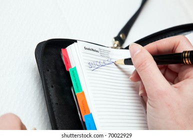Woman writing the word success on her agenda