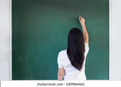 Woman writting on green board