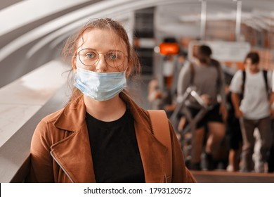 A woman in the wrong medical mask is standing in the subway. The protective mask is not properly worn on the face of a woman in transport