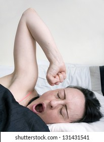 woman yawning and stretching in bed, portrait with copy space