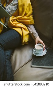 Woman in yellow blanket drinks coffee and reads book