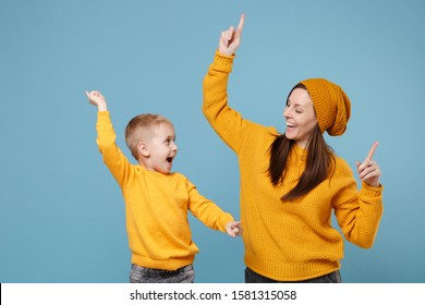 Woman in yellow clothes have fun posing with cute child baby boy 4-5 years old. Mommy little kid son isolated on blue background studio portrait. Mother's Day love family parenthood childhood concept