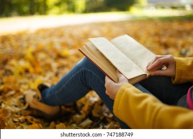 The woman in yellow coat and jeans sitting under the maple tree with a red book in fall city park on a warm day. Autumn golden leaves. Reading concept. Close up.