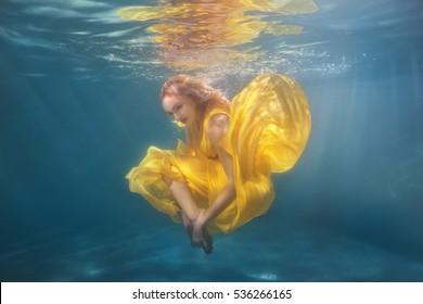 Woman in yellow dress dancing underwater showing figures.