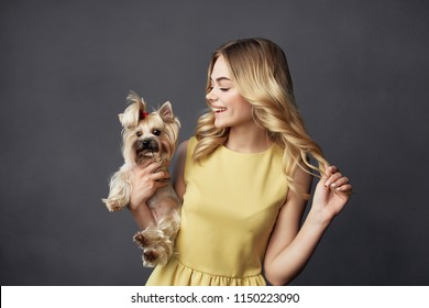 a woman in a yellow dress is holding a thoroughbred puppy