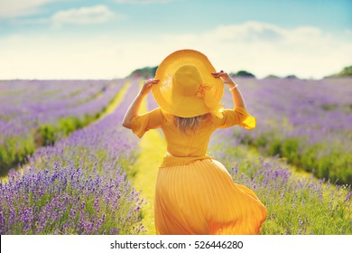 woman in a yellow dress with a lavender field in english garden