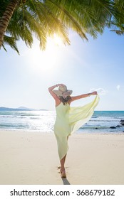 Woman in yellow dress walking on the beach under the coconut tree