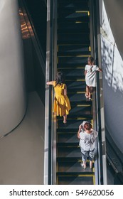 woman in yellow. escalator woman in yellow dress, woman in modern dress people on escalator going up