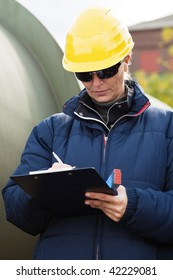 Woman in yellow hard hat taking notes while standing in a construction site