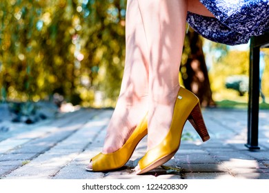 A woman in yellow high-heeled shoes against the backdrop of nature sits cross-legged.