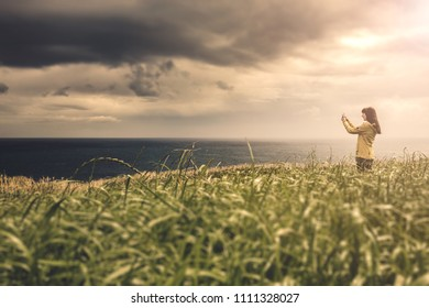 Woman with a yellow jacket looking to the ocean